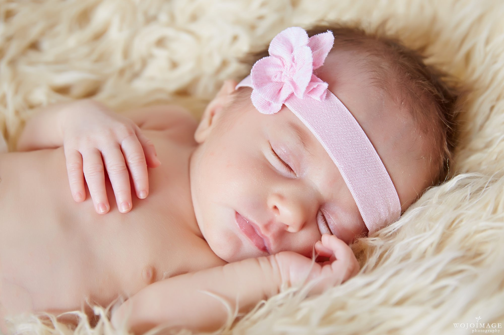 Natural Newborn Baby Lifestyle Pose on a Furry Blanket