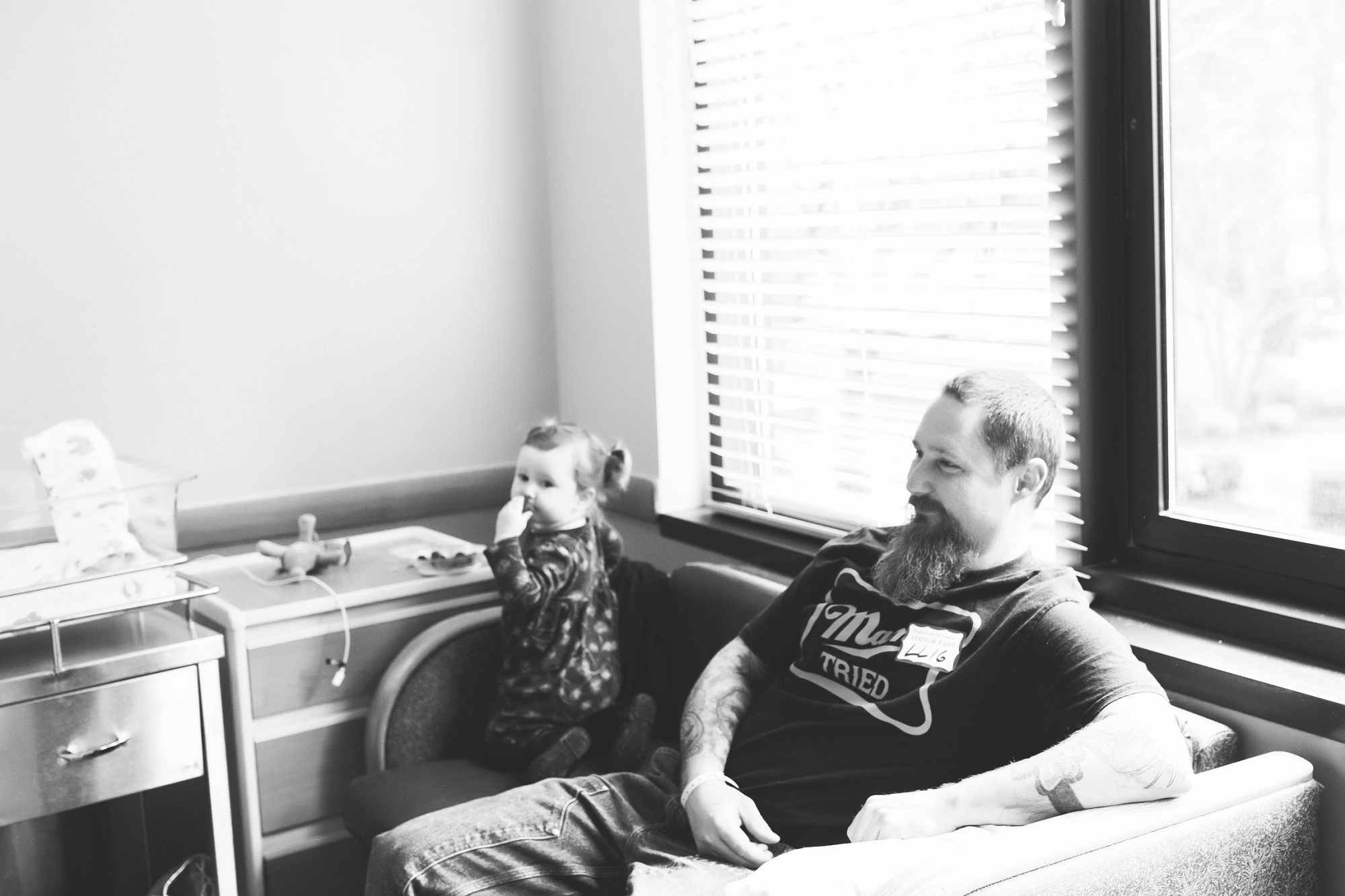 dad and daughter watching newborn baby