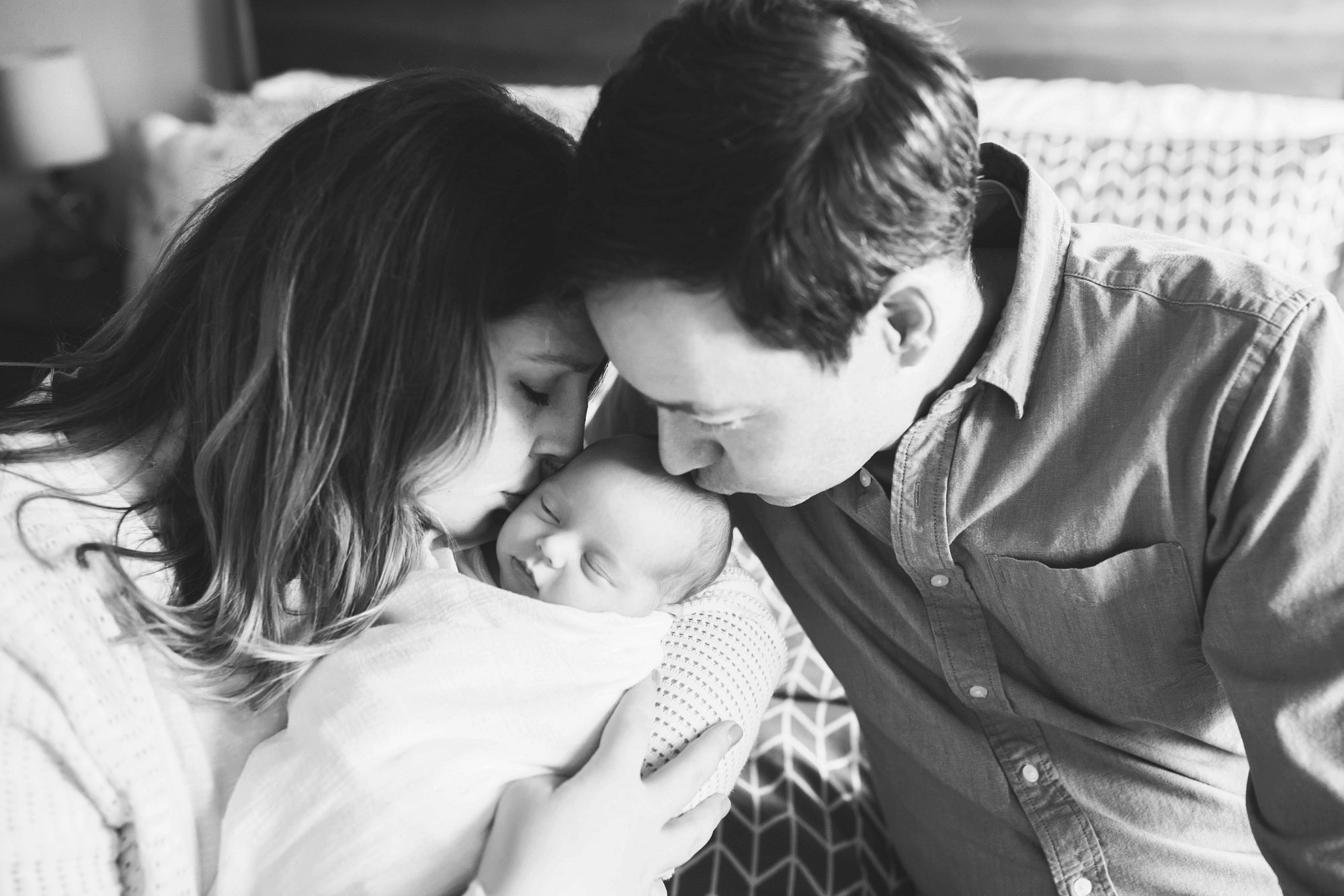 parents kissing newborn baby