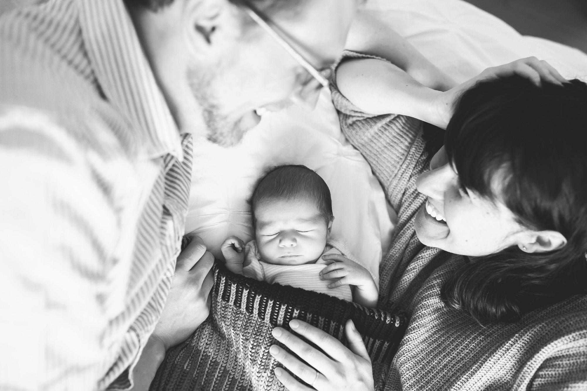 parents laying in bed with newborn baby