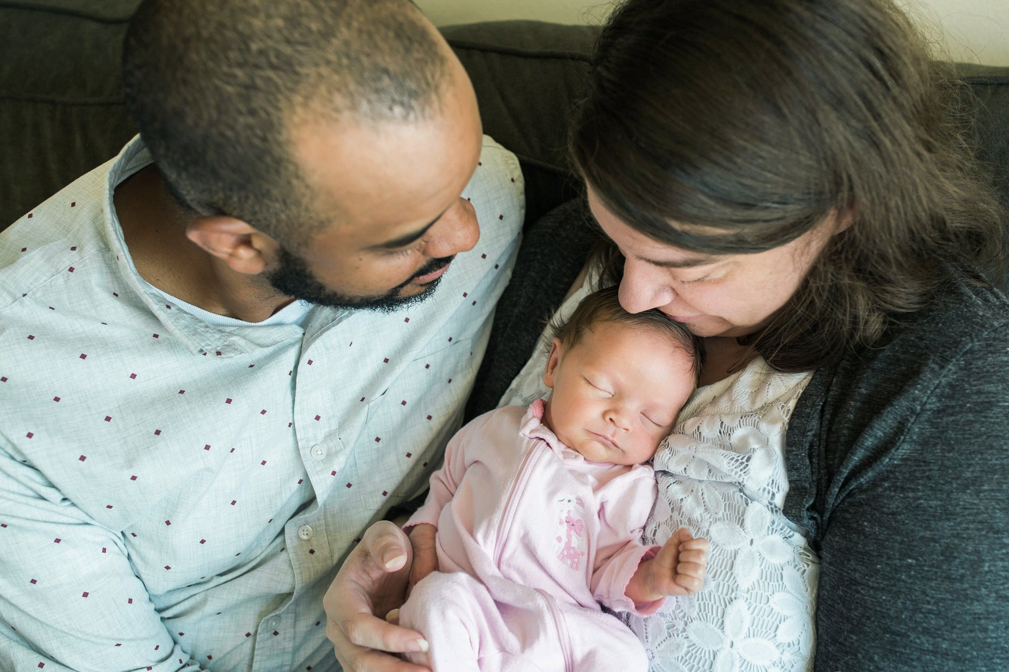 parents holding newborn baby girl at home