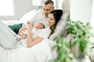 parents laying on bed with their newborn baby