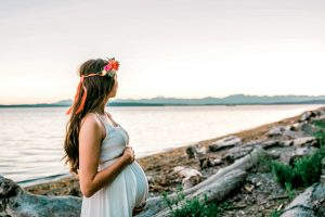 pregnant woman holding her belly by the beach in Seattle