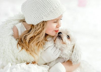 little girl kissing her dog