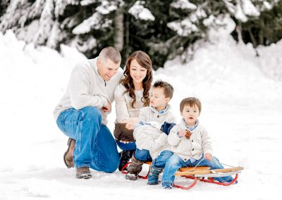 family sitting on sled
